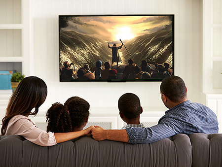 Family sitting on couch watching Moses part the Red Sea on the big screen TV
